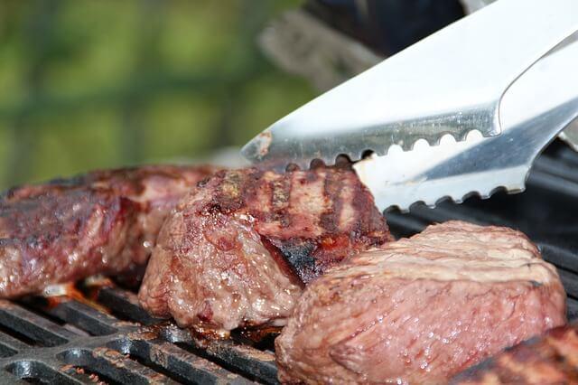 Gegrilltes Steak mit einer Grilllzange