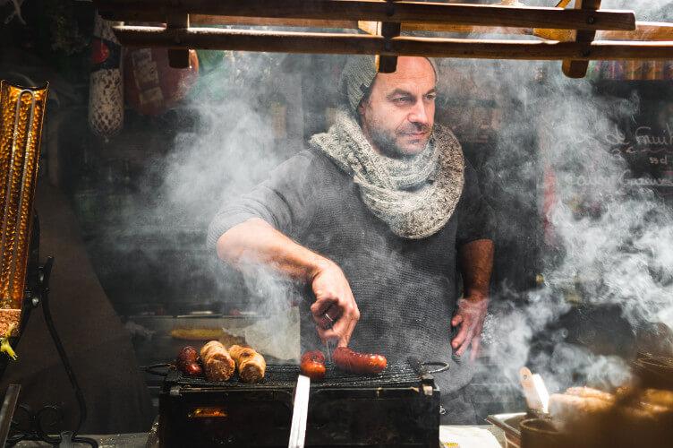 Mann grillt Bratwürstchen