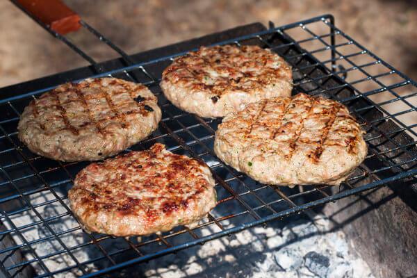 4 Burger-Patties auf einem Grillrost