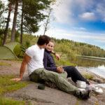 Mann und Frau grillen im Freien beim Camping